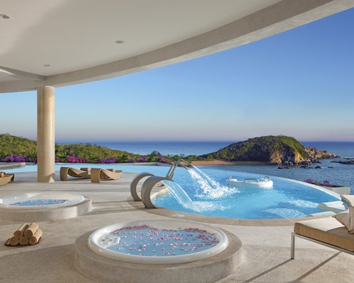 A swimming pool with water feature hot tubs and the ocean view.
