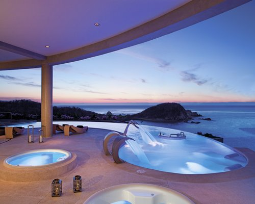An outdoor swimming pool and hot tub with chaise lounge chairs alongside the ocean.