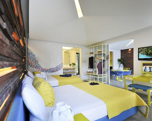 A well furnished bedroom with a television dining table and two beds.