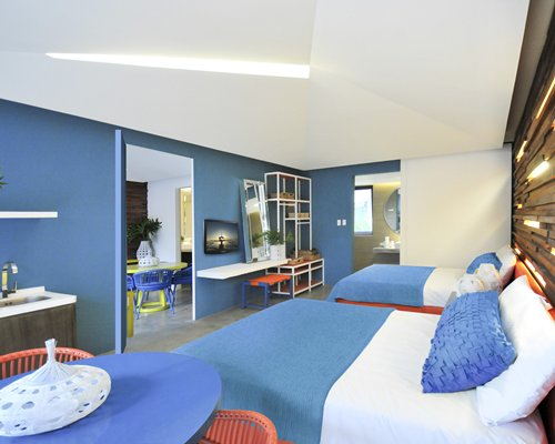 A well furnished bedroom with two beds a television and dining area.