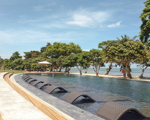 An outdoor swimming pool with chaise lounge chairs and sunshades alongside trees.