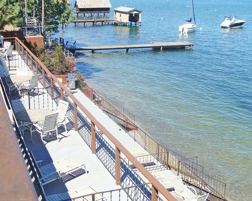 Balcony with patio furniture alongside the lake with a wooden pier and boats.