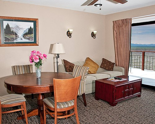 A well furnished living room with a dining area and balcony.