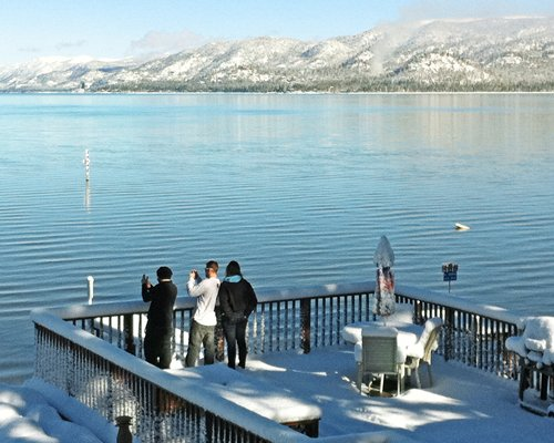 People at an outdoor dining area alongside the lake and mountains.