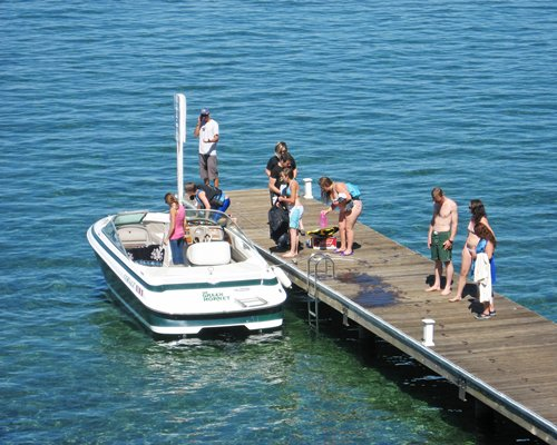 People on a wooden pier and boat outside of the resort.