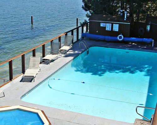 An outdoor swimming pool and hot tub with chaise lounge chairs alongside the lake.