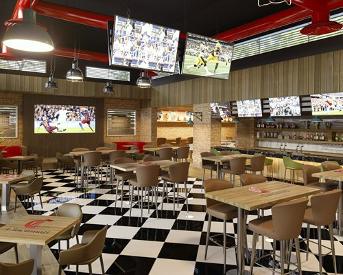 An indoor sports bar with multiple dining tables.