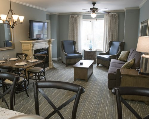 A well furnished living room with a television fireplace and dining area.