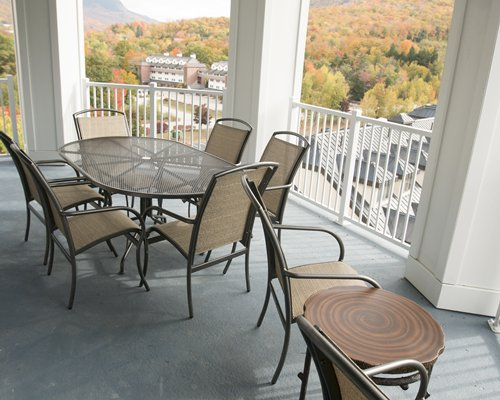 View of buildings and wooded area from the balcony with dining area.