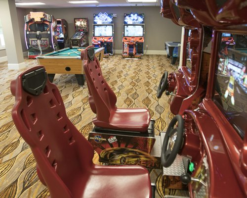An indoor recreational area with a pool table and arcade games.
