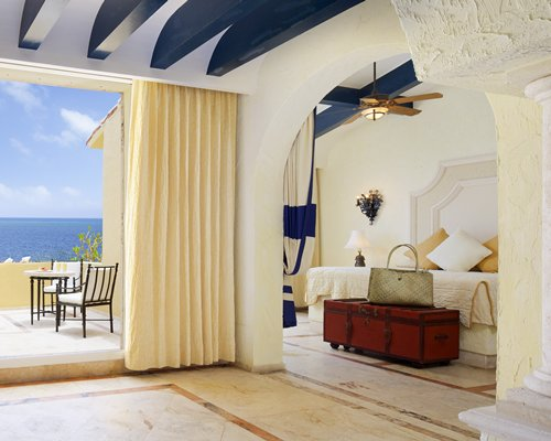 A well furnished bedroom with a view of the sea.