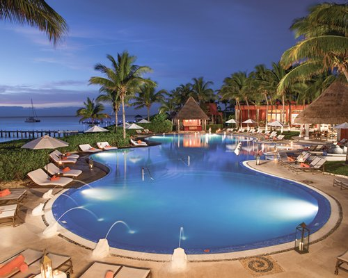 An outdoor swimming pool with sunshades and chaise lounge chairs at night.