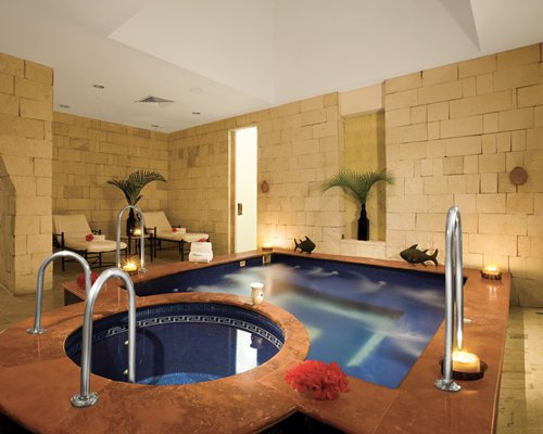 An indoor swimming pool with a hot tub and chaise lounge chairs.