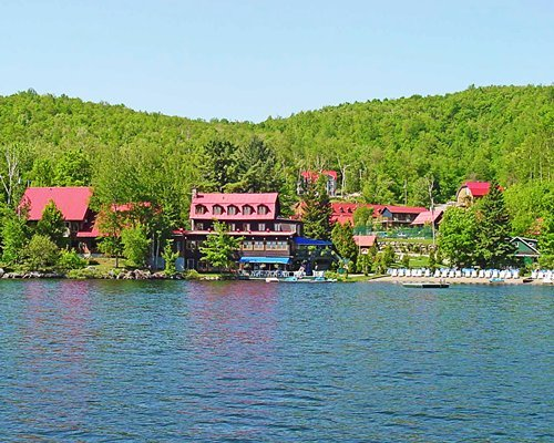 Exterior view of the resort surrounded by wooded area alongside the lake.