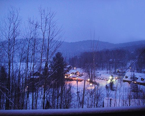 Exterior view of Auberge du Lac Morency at a snowy area surrounded by woods at dusk.