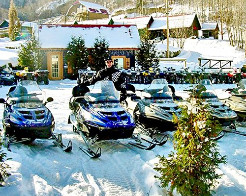 View of snowmobiles alongside the resort unit covered in snow.