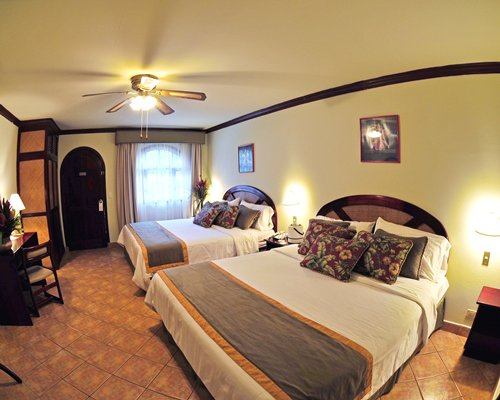 A well furnished bedroom with two queen beds and an outside view.