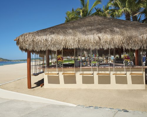 A poolside bar with hut along side thatched sunshades.