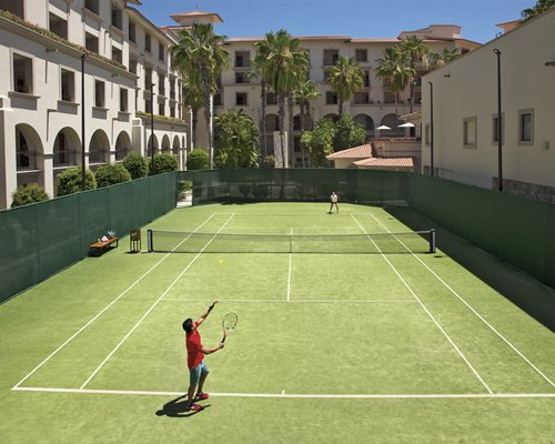 Outdoor tennis courts alongside resort.