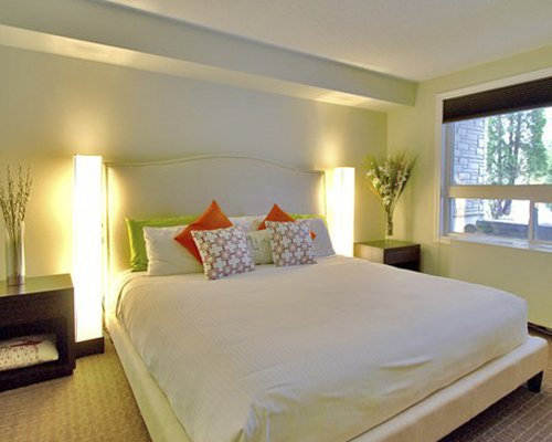 A well furnished bedroom with lamps and outside view.