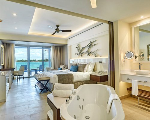A well furnished bedroom with bathroom and balcony.