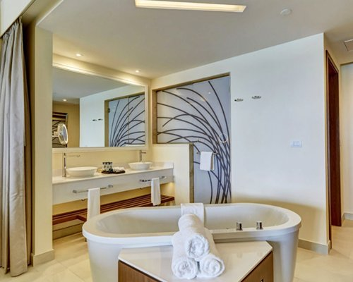 A bathroom with double sink vanity, shower, and bathtub.