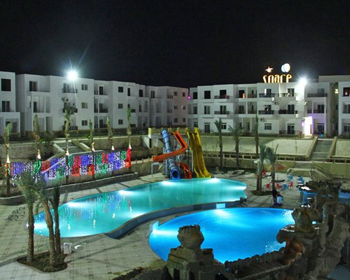 An exterior view of resort and pools with lights at night.
