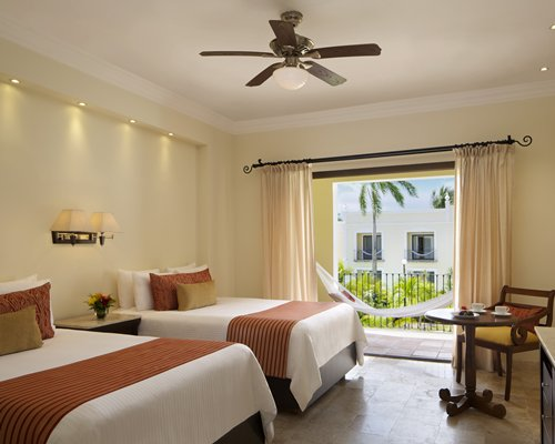 A well furnished bedroom with two twin beds patio and hammock.