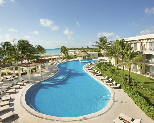 An outdoor swimming pool with chaise lounge chairs alongside the resort.