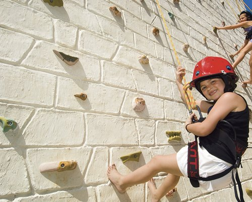 View of kids on an outdoor rope climbing wall.