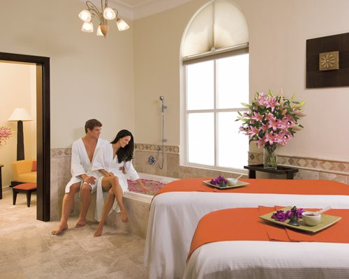 A couple relaxing in an indoor spa with a bathtub.