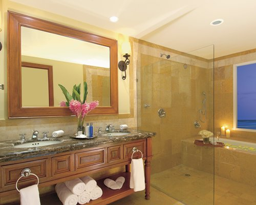 A bathroom with bathtub shower and a double sink vanity.