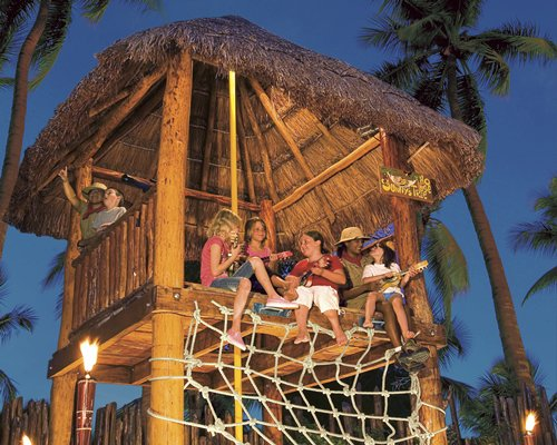 View of people at a thatched covered wooden deck surrounded by palm trees.