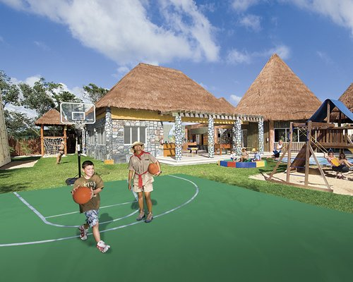 An outdoor kids playscape and a basketball court alongside the resort units.