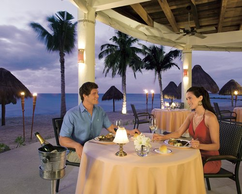 Couple at an outdoor dining area alongside the beach with thatched sunshades and palm trees.