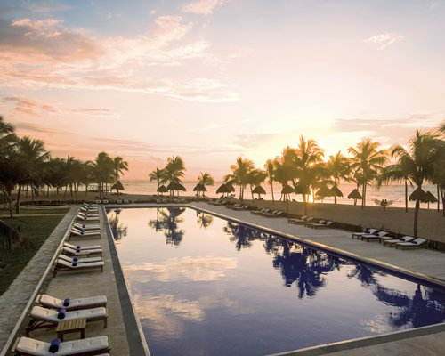 An outdoor swimming pool with chaise lounge chairs and trees at dusk.