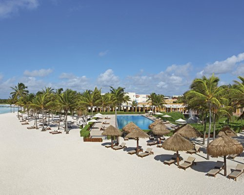 An outdoor swimming pool with chaise lounge chairs and thatched sunshades alongside the ocean.