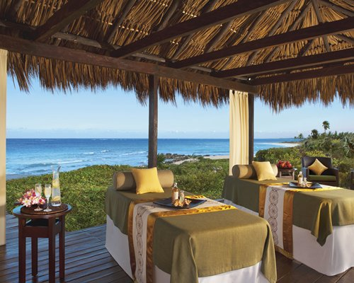 Thatched covered spa with massage beds alongside the beach.