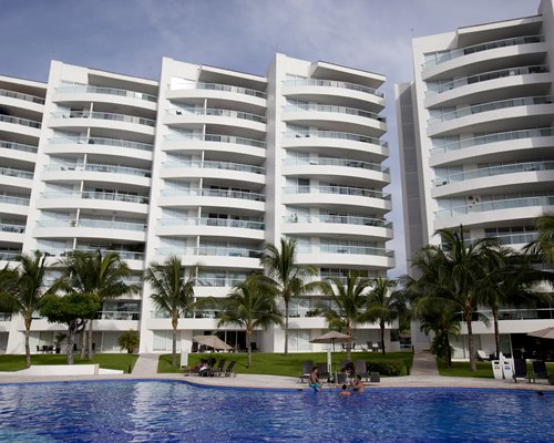 Scenic exterior view of Dreams Villamagna with large outdoor swimming pool and sunshades.