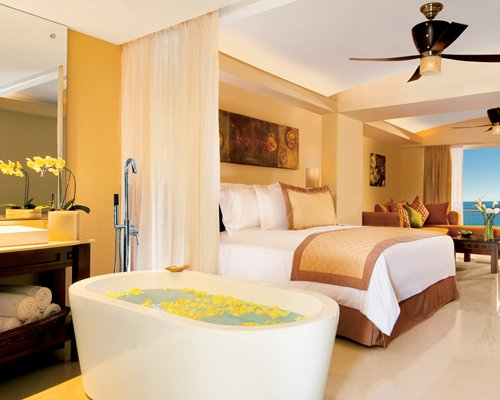 A well furnished bedroom with a shower and bathtub.