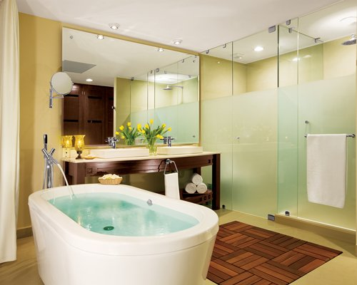 A bathroom with a bathtub shower and double sink vanity.