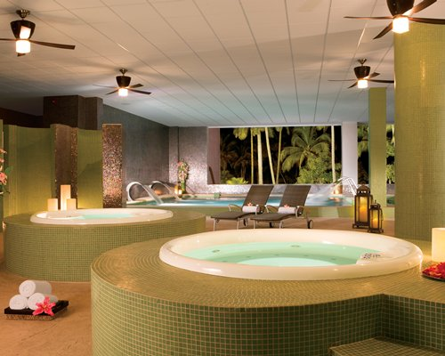 An indoor swimming pool and two hot tubs with water curtains and chaise lounge chairs.