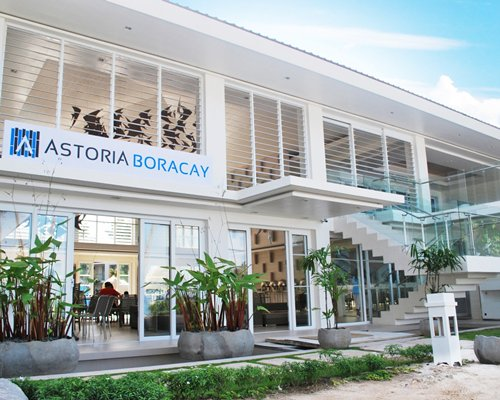 An exterior view of Astoria Boracay resort with potted plants.
