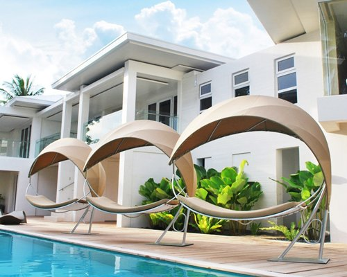 View of garden furniture alongside the swimming pool and multi story resort units.