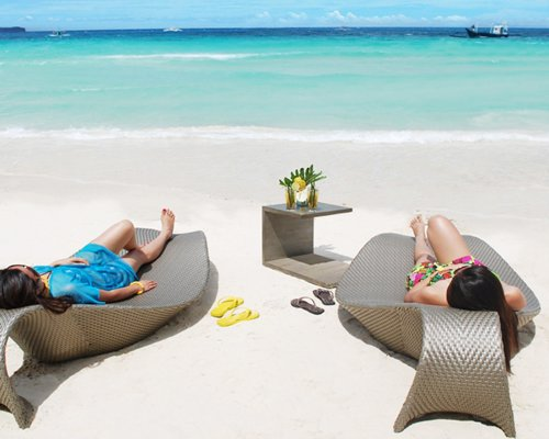 Beach view of two women lying on the chaise lounge chairs facing the sea.