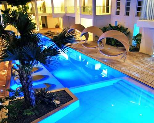 An outdoor swimming pool with garden furniture alongside resort units at night.