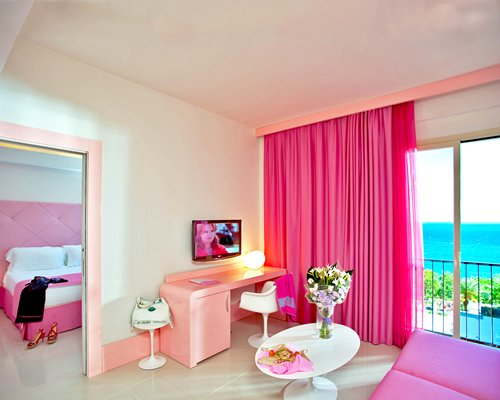 A well furnished living room with a television and balcony alongside a bedroom.