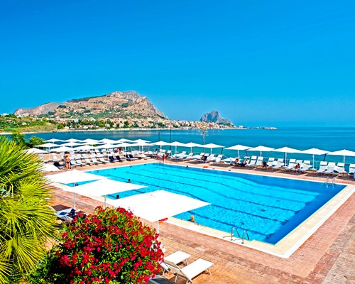 An outdoor swimming pool with chaise lounge chairs and sunshades alongside the sea.