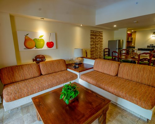A well furnished living room with open plan kitchen and breakfast bar.