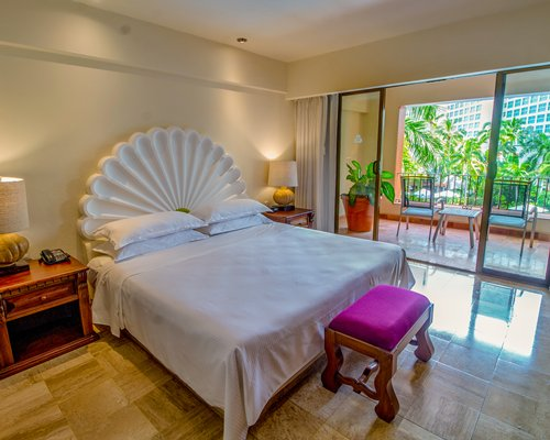A well furnished bedroom with a bathtub balcony and ocean view.